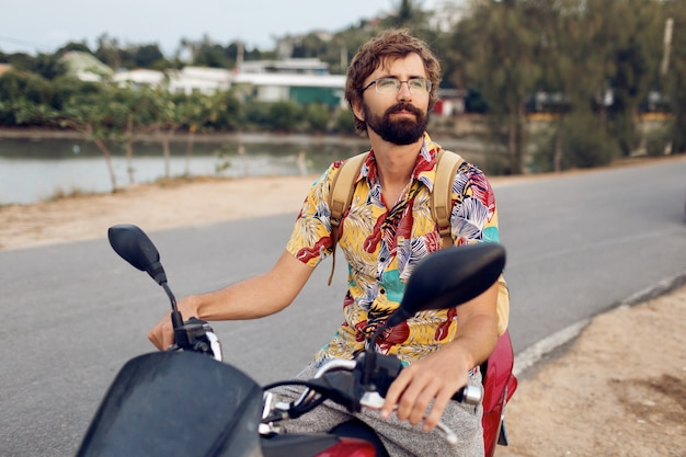 Человек с бородой в красочной тропической рубашке сидит на мотоцикле