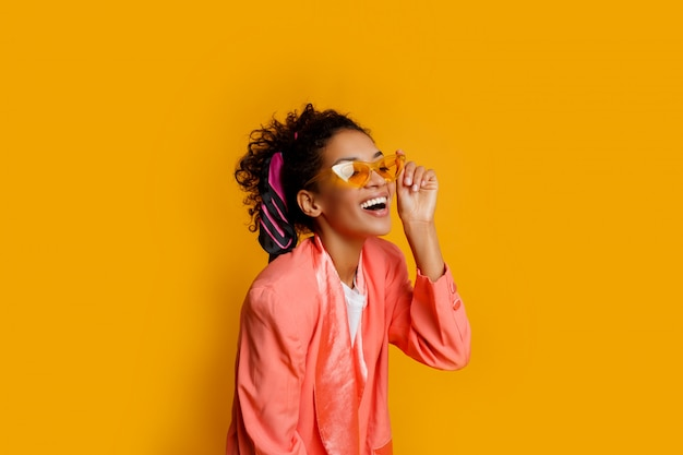 黄色の背景に幸せそうな表情でポーズピンクのジャケットの素敵なアフリカの女の子。