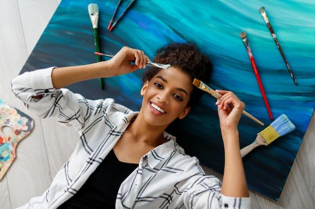 手にブラシでキャンバスの上に横たわる幸せな画家の女性の平面図です。生産的な仕事の後の夢とリラックス。