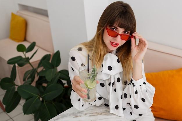 Стильная женщина сидит в кафе и пьет коктейли