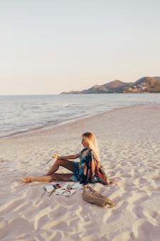 Блондинка рисует акварелью цветок кистью на пляже