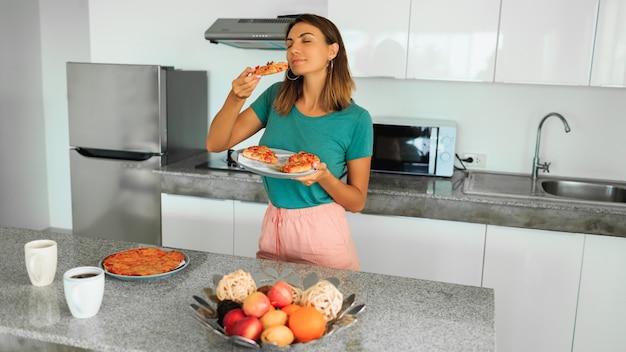Брюнетка счастливая женщина, держа тарелку с пиццей на кухне в современном доме
