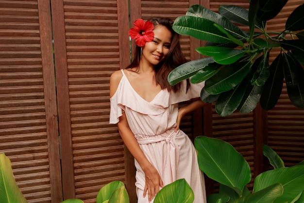 Грациозная азиатка с идеальной кожей и цветком гибискуса в волосах позирует на деревянной стене