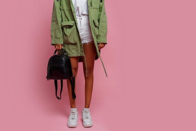 ファッションの詳細。緑のジャケット、白いショートパンツ、スニーカーでピンクの背景のスタジオで立っている黒人女性。