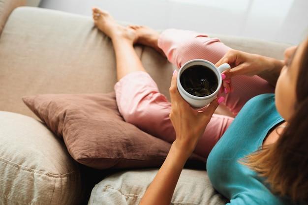 お茶のカップを保持している、ウィンドウを見て、モダンなソファでリラックスできる居心地の良い家庭服のブルネットの女性