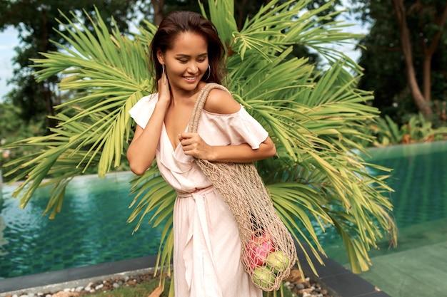 無駄のないコンセプト。新鮮な果物と環境に優しいメッシュの買い物客を保持しているアジアの女性。