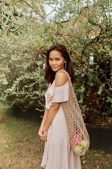 新鮮なトロピカルフルーツを使った環境にやさしいメッシュショッパーバッグを保持しているドレスを着たアジアの女性。