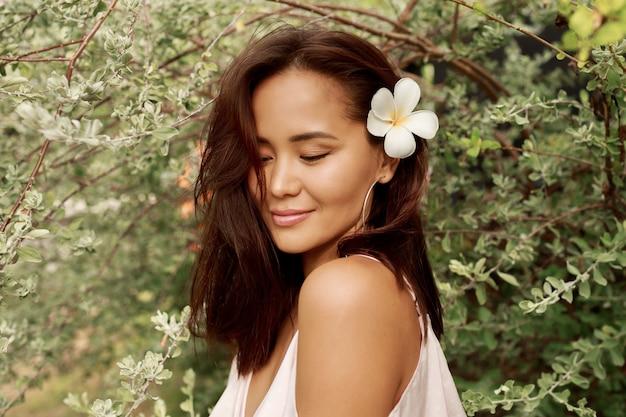 Портрет лета симпатичной азиатской женщины с цветком в волосах представляя в саде.