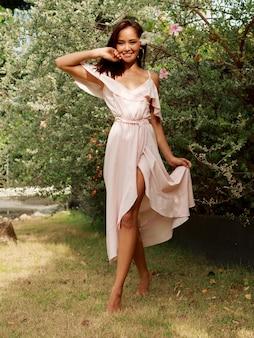 夏の庭でポーズをとってピンクのドレスで率直な笑顔で幸せなアジア女