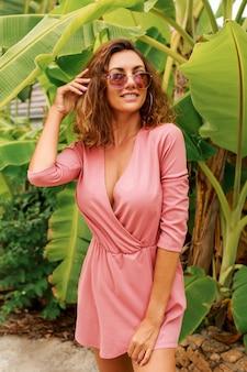 ヤシの木の上に立っているピンクのドレスで巻き毛を持つセクシーなヨーロッパの女性。夏のファッション。