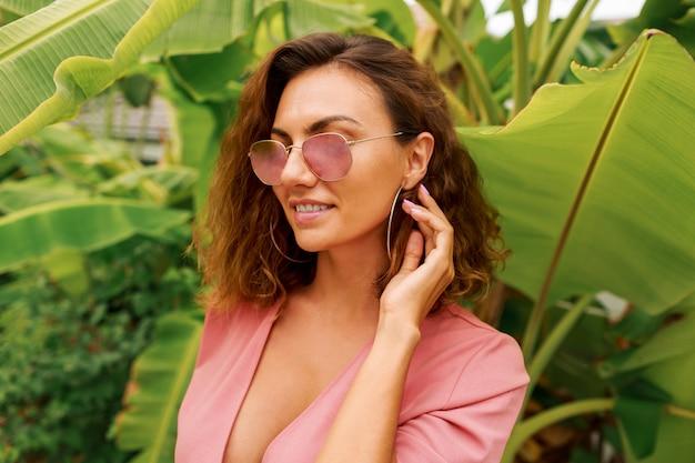 Сексуальная европейская женщина с вьющимися волосами в розовом платье, стоя над пальмами.
