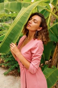 Открытый летний портрет соблазнительной брюнетки с волнистыми волосами в розовом платье позирует