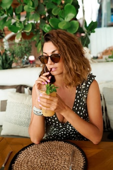 レモネードを飲んで、居心地の良いカフェで身も凍るようにトレンディな夏の服装で笑顔の巻き毛の髪の女性。