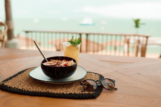 アジアリゾートのビーチ近くのカフェで新鮮なトロピカルオーガニックスムージーボウル。