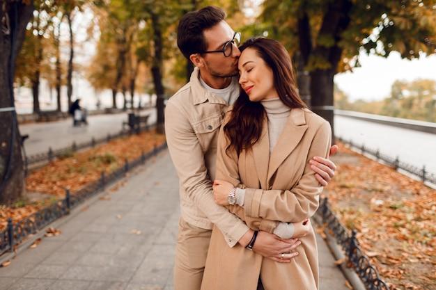 ロマンチックな瞬間。恋に浮気し、素晴らしい秋の公園で楽しんで幸せな美しいカップル。