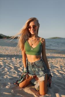 Сексуальная белокурая женщина в зеленой верхней части и джинсах представляя на тропическом пляже.
