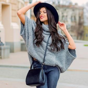 トレンディな秋の服、黒い帽子、灰色のセーター、革のバッグを身に着けているグラマー官能的な若いスタイリッシュな女性のアウトドアファッションの肖像画。真っ赤な唇。旧市街の背景。