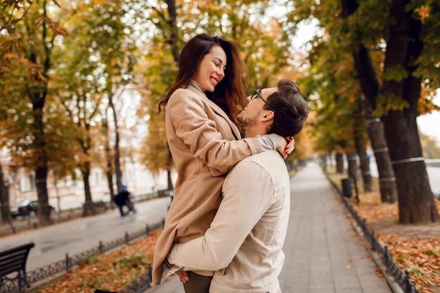 秋の公園でデートしながら恥ずかしいファッショナブルな男と女。スタイリッシュなベージュのコートを着ています。ロマンチックな気分。