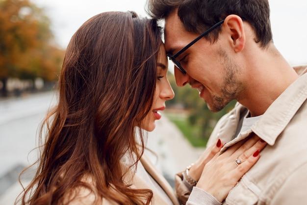 秋の公園でデートしながら男と女が恥ずかしい。スタイリッシュなベージュのコートを着ています。ロマンチックな気分。