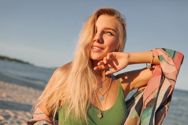 Крупным планом портрет соблазнительной белокурой женщины на пляж заката.
