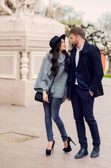 日当たりの良い秋の古い通りでポーズの若者のファッションのカップル。かなり美しい女性と彼女のハンサムなスタイリッシュなボーイフレンドが路上で抱き締めます。
