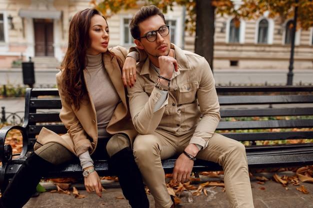 愛の屋外ポーズでスタイリッシュなカップル。秋のファッショントレンド。ベンチに座っているベージュのコートを着たスタイリッシュな男とブルネットのモデル。