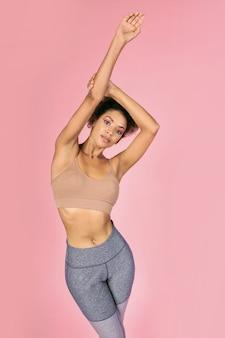 スタイリッシュなスポーツウェアで優雅なミックスレース女性がスタジオでピンクの背景にポーズします。
