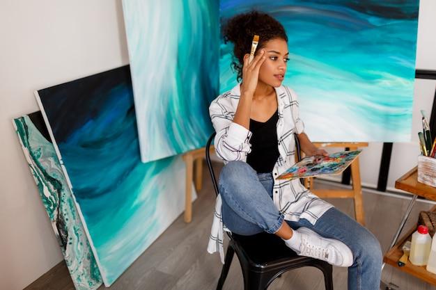 スタジオのキャンバスに絵を描くプロの女性アーティストの肖像画。彼女のワークスペースで女性画家。