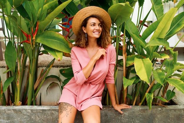 ピンクのドレスのポーズでウェーブのかかった毛を持つ魅惑的なブルネットの女性の夏の屋外の肖像画