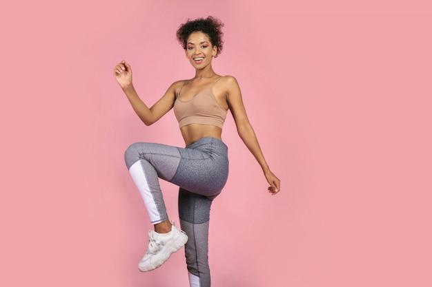 スポーティな女性がスタジオでスクワットの練習を練習します。ピンクの背景でワークアウトのスポーツウェアでアフリカの女性。