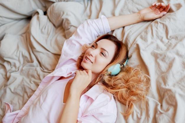 目を覚ました後ベッドでストレッチイヤホンで美しい生姜少女は完全に休んだ。