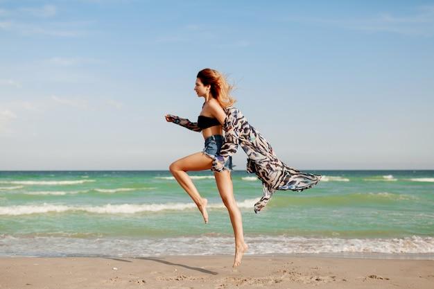 オーシャンリゾートで地平線ビューを楽しんでいるかなりスリムな女の子の全身像》。