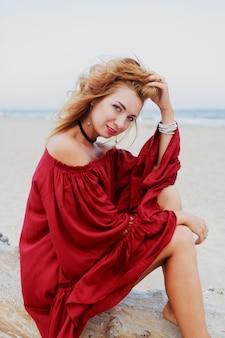 Веселая рыжая девушка позирует на пляже. сидеть на белом песке. ветреные волосы. модный наряд. образ жизни портрет. настроение путешествия берег океана.
