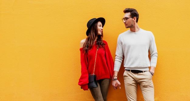 恋に手をつないで、お互いに喜びを探してエレガントなスタイリッシュなカップルの秋のファッション画像。彼女のボーイフレンドのポーズと赤いニットセーターの長い髪の女性
