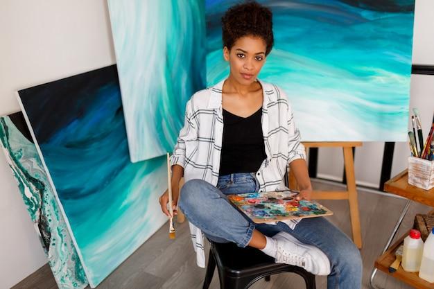 スタジオのキャンバスに絵を描く女性アーティスト。彼女のワークスペースで女性画家。
