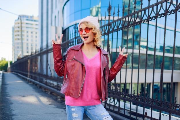 トレンディなピンクの帽子、革のジャケットでうれしそうな流行に敏感な熱狂的な女性の屋外のポートレート。手で標識を示しています。