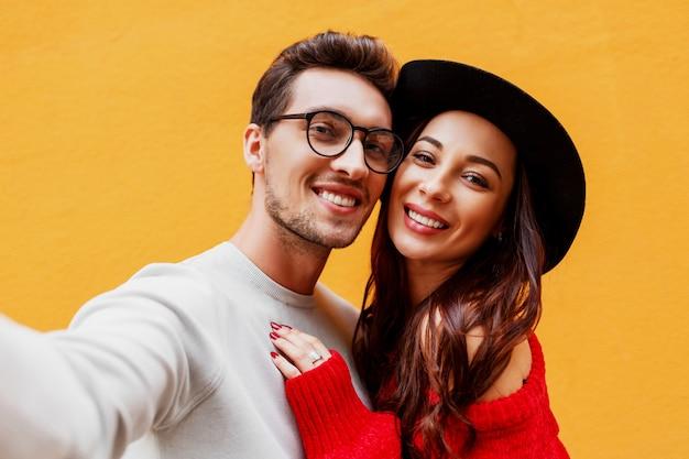 携帯電話でセルフポートレートを作る彼女のボーイフレンドと一緒に幸せな女の子のライフスタイルの肖像画を閉じます。黄色の壁。赤いニットのセーターを着ています。新年のパーティー気分。