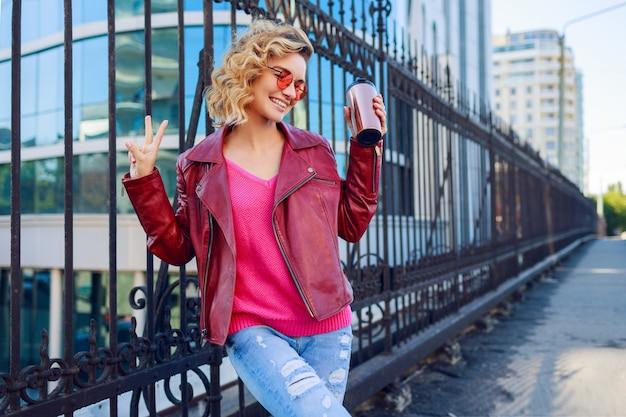 モダンな通りでポーズをとって、コーヒーやカプチーノを飲んで幸せな金髪女。スタイリッシュな秋の服、革のジャケット、ニットのセーター。ピンクのサングラス。