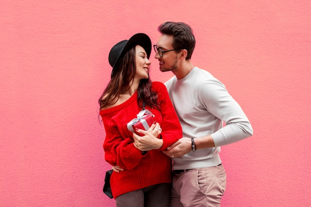 手を繋いでいると喜びでお互いを見ている愛のエレガントなスタイリッシュなカップル。彼女のボーイフレンドのポーズと赤いニットセーターの長い髪の女性。
