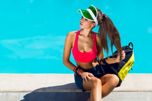 夏の暑い日にプールのそばに座ってスポーツスタイリッシュな服で若い魅力的な女性。パーフェクトな日焼けスリムボディ。