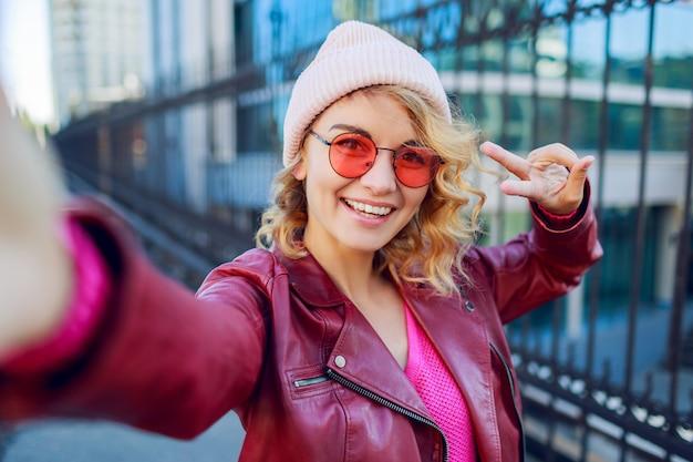 トレンディなピンクの帽子、革のジャケットでうれしそうな流行に敏感な熱狂的な女性のセルフポートレートを閉じます。手で標識を示しています。