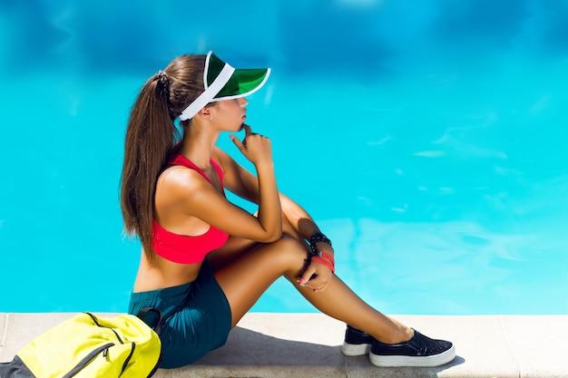 夏の暑い日にプールのそばに座ってスポーツスタイリッシュな服装で新鮮な健康的な若い魅力的な女性。パーフェクトな日焼けスリムボディ。