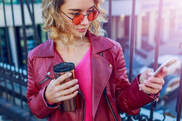 街を歩いて、スマートフォンを使用して若い夢のようなブロンドの女性。詳細を閉じます。コーヒーとスタイリッシュなモダンな女の子。風の強い髪。