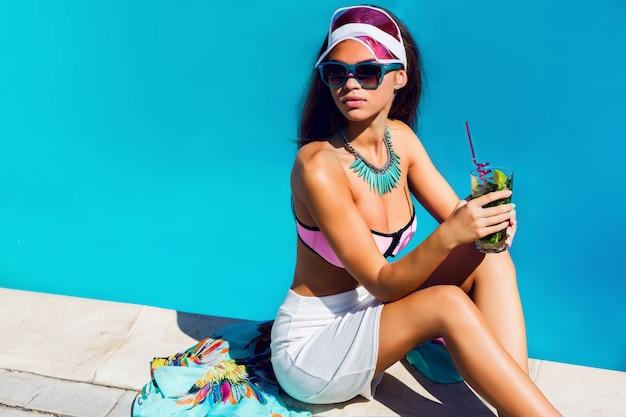 ピンクのスタイリッシュなビーチ服とスイミングプールのそばに座って明るい色のアクセサリーで日焼けした美しい若いモデル。ファッショナブルな肖像画。