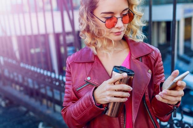 Молодая мечтательная белокурая женщина гуляя в город и используя умный телефон закройте детали. стильная современная девушка с кофе. ветреные волосы.