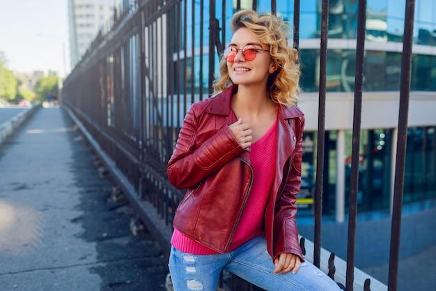 トレンディな革のジャケットでうれしそうな流行に敏感な熱狂的な女性の屋外のポートレート。手で標識を示しています。