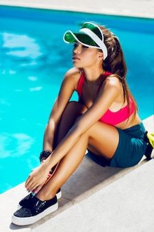 夏の暑い日にプールのそばに座ってスポーツスタイリッシュな服で健康的な若い魅力的な女性。パーフェクトな日焼けスリムボディ。