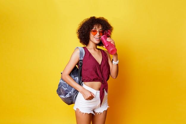 優雅なスポーツの黒の女性が黄色の背景の上に立って、ピンクの水のボトルを保持しています。スタイリッシュな夏服とバックパックを着用。