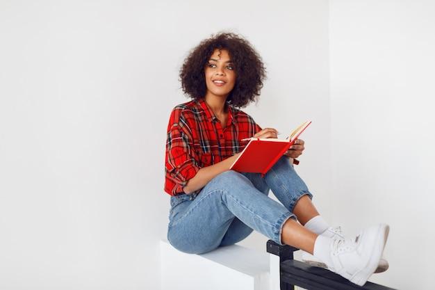 Задумчивая африканская девушка студента отдыхая с тетрадью. одет в красную клетчатую рубашку. синие джинсы.