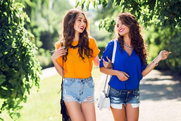 Две красивые девушки гуляют в парке летом и разговаривают